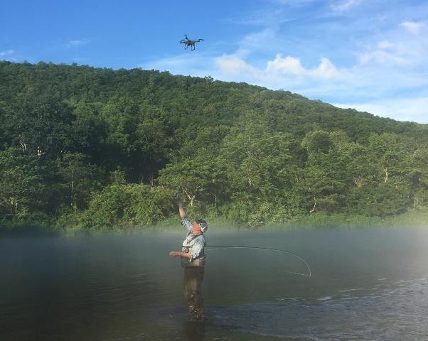Dave getting a drone beer delivery on the West Branch after landing a fish.  Photo by Beth Zmijewski